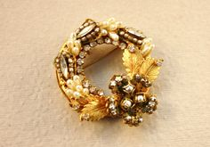 "This love brooch consists of two types of faux pearls, numerous pronged set rhinestones gilded gold leaves set in a filigree setting. It is in a wreath shape & measures 2"". Original by Robert logo 1955-1979 composed of Robert Levy, David Jaffe, and Irving Landsman began as Fashioncraft Jewelry Co.,NYC 1942. 