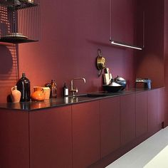 monotone kitchen in dark red with black accents ...via Studio J. Interiors