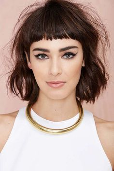 shoulder length brown colored bob hairstyle with very short bangs