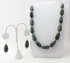 Classy and beautiful. Necklace and earrings feature honey and dark aqua porcelain beads.    Necklace: 25 long  Earring: French Hook