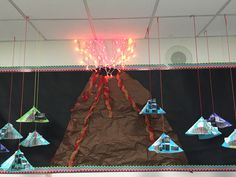 Volcano bulletin board. I used red and orange Christmas lights for the explosion above the volcano crater. I then used red and yellow wired ribbon as the lava oozing down the side. I crumpled the brown paper to establish texture. Volcano foldables hang from the ceiling on both sides like mobiles.
