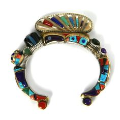 128.8g, 0.5'' bandwidth, the 7'' size includes a 1'' gap. Stones include turquoise, coral, lapis, opal, jet, spiny oyster, fossilized ivory, and sugilite. Acquired from a private collection out of Santa Fe, NM.
