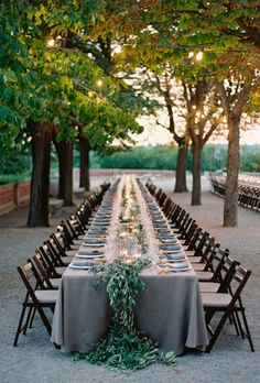 Love the one long table and garland... grey linens also nice - wood chairs - simple and nice but maybe too austere?