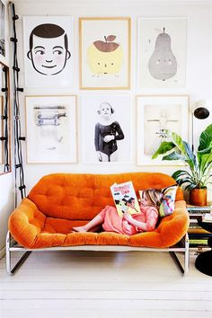 orange sofa, white floors, gallery wall