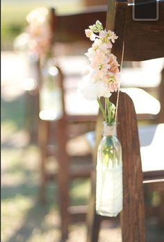 I would like to on each row down the aisle do something like this whether its a bottle like this, a mason jar w/ a handle, or something else. Flowers to match the wedding colors...babys breath, something orange and maybe a short peacock feather to tie it in