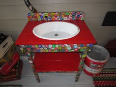 Outdoor sink made from 1300 bottle caps and an enamel ware dish pan.  Once completed, an exterior car finish was sprayed on top.