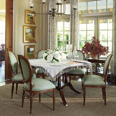 Love a round dining room table...and in this room love the tall windows and drapes.