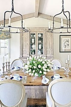 The 2 chandeliers work well with a rectangular table & I like the worn Country French look of the room.
