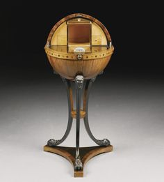An Austrian rosewood, fruitwood, ebonised and penwork table, Viennese circa 1820 - Sotheby´s - in the form of a celestial globe decorated with signs of the zodiac and opening to reveal a fitted architectural interior concealing secret compartments and drawers, raised on three curved ebonized supports with lion heads and paw feet, on a triangular concave-sided plinthn rosewood, fruitwood, ebonised and penwork table, Viennese circa 1820