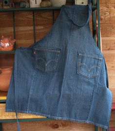 Perfect for the workshop, craft room, cooking and barbequing, a denim apron with 2 front pockets and made from upcycled jeans, is sturdy and just right for men or women!  This apron was made from a well known brand of mens jeans. Although sized to fit most, the apron shown is closely sized to a mens large. It is a grey blue in color. The apron has an adjustable neck tie to allow the wearer to position the bib top high or low for a comfortable, individual fit. Size: one size fits most Width…