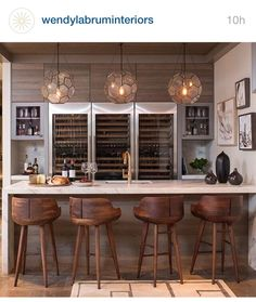 three arteriors beck pendants a marble waterfall bar fitted with a wet bar sink and gold gooseneck faucet lined with wood counter stools