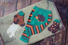 Brown, orange and green striped leggings with a super cute hedgehog on the bottom by Blade & Rose