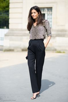 chic transitional look for September – Barbara Martello wearing a silk cheetah print blouse and elegant black high-waisted trousers  outside the Dior couture show