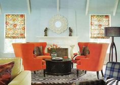 4 wing chairs surrounding round ottoman in front of fireplace.  round mirror.  flanked by windows.  floor lamp.  betsy burnham via danielle oakey