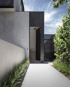 The Kooyongkoot Road Residence by B.E Architecture builds on the client's interest in a sleek, clean-lined aesthetic. The design response developed a series of details in thin black steel in contrast to the light spaces. One of these details is the front pivot door, clad in back steel which is soften with the textural render and green plantings leading up to the entry.