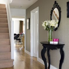 A textured wallpaper, decorative mirror and high-gloss table add a little luxury to this neutral hallway.