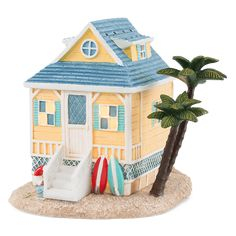 Feeling landlocked? This quaint little seaside cabin complete with palm tree brings the getaway to you with sun-drenched color, hand-painted detail and funky beach town attitude.