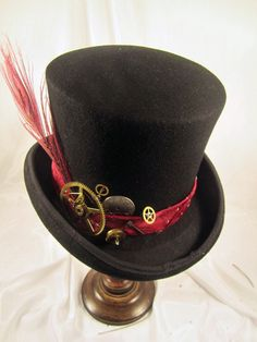 Steampunk Men's Black Bell Topper with Tie band and Clock parts. New SteamPunk Black Bell Topper Men's Hat with men's tie band, clock parts, peacock feather and key. All our Steampunk hats are made with real clock and watch parts making each hat a unique work of art. (each hat is hand made with real parts and will vary slightly from image shown).