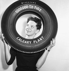 A woman poses with a Firestone tire to mark the 1,000,000th produced at a plant in Calgary, Alberta. #1960s #vintage #Canada