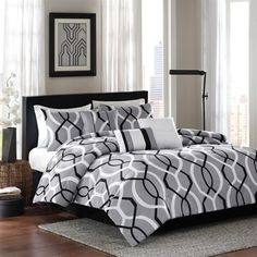 Make a contemporary statement in your bedroom with the Ellie collection. The comforter and shams feature a bold, circular geometric pattern in black and white against a grey ground reversing to a solid light grey color. The set includes a solid black bedskirt. Three pintucked and pieced decorative pillows add dimention and texture to the whole look.