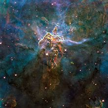 "To commemorate Hubble Telescope's 20th anniversary, NASA, with ESA and STI, released this Wide Field Camera 3 shot of a portion of Carina Nebula, dubbed ""Mystic Mountain"". Taken in February 2010, oxygen is colored blue, hydrogen and nitrogen green, and sulfur with red"