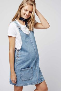 Keep denim looking current throughout your pregnancy in this MOTO pinafore dress. A boxy silhouette cut with a scoop neckline and deep patch pockets to the front. Team it with a black long sleeve top to finish the look. #Topshop
