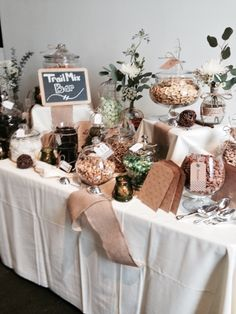 Mix it up with this fun favor idea! Treat your guests to a create-your-own trail mix bar on your special day. Display created with apothecary jars, chalkboard signs, greenery for color, and an array of textiles/textures.
