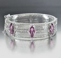 Brilliant faceted open back amethyst purple stones take on a unique shape in this rhodium silver filigree Art Deco bangle bracelet circa 1920s.  The bangle has