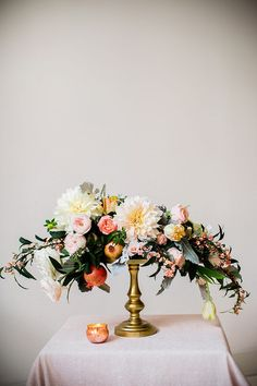 Designed by Juli Vaughn, this decadent Flemish-style floral arrangement featured dinner-plate dahlias, garden roses, dusty miller foliage, and fresh pomegranates.   Photo by Betsi Ewing