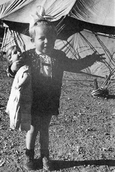 A child of two and a half, a large bow tied in her hair, clutching a doll – so far, perfectly ordinary. But in the background are tents that tell a story of wandering and transience and a barbed wire fence that testifies to a life in confinement. Thus, in one snapshot, the photographer immortalized the early childhood of Vera Brand, born into the reality of war. Read more...