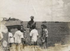 Children surround a soldier of the 9th Infantry Div.
