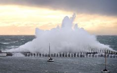 A waves crashes over Mornington Pier during strong winds in Victoria, Australia