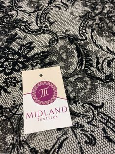 Untitled Document Black flock lace effect off white Jersey fabric 2 way stretch 58 M16-21 Mtex Width 58in Sample Size approx 10cm x 10cmPlease