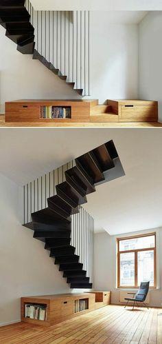escalier design en métal noir, noir total, forme angulaire, garde corps en forme de rayures régulières noires, parquet clair beige, grande fenêtre au cadre en bois clair, petit meuble bibliothèque qui sert de base à l'escalier