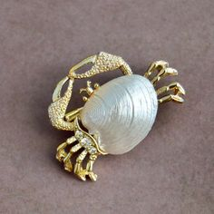Mint condition, vintage Gerrys, gold tone crab brooch/scatter pin, with three clear rhinestones and shell accent. GERRYS and copyright mark on back