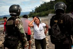 A woman cries in front of police after authorities destroyed her canoe's engine, which partially destroyed her boat, for allegedly transporting machinery used by illegal gold miners at the Punkiri dock.  'Illegal Gold Mining in Peru- In Photos'