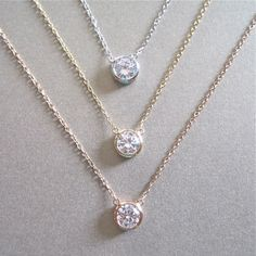 This solitaire cubic zirconia necklace is great for layering with other styles. The 0.5 carat stone is framed and attached at separate points to the chain. Available in sterling silver, 14tk gold fill