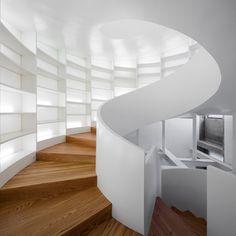 Esta escada em espiral não só conecta dois andares, mas também oferece espaço para armazenamento de livros. Ela foi projetada pelo arquiteto português Manuel Maia Gomes