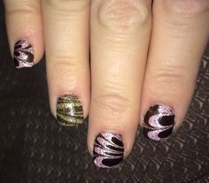 Pink glitter polish and gold glitter polish. Black and top coat water marble on top of glitter polish.
