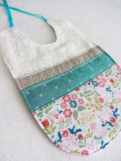 Bavoir, serviette de table en tissu éponge écru décoré devant, d'un coton blanc à  motifs  fleurs (rose, vert d'eau bleu) de deux bandes de tissu aux couleurs (gris à pois, t - 18849833
