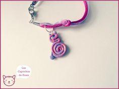 Pulsera hecha a mano con cola de ratón fucsia y organza lila, adornada con espiral de fimo en forma de gato en tonalidades similares, decorado con purpurina.