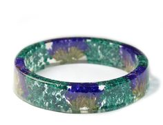 *This item is MADE TO ORDER Please allow approximately 2 weeks processing time   MEASUREMENTS- 5/8 inch wide with 2 5/8 inner diameter * ONLY SIZE AVAILABLE  **************************************************************************  This lightweight slip on style bangle is made with beautiful purple and teal colored flowers embedded into resin and shaped into this one of a kind bracelet.  Our artisan bangles are created by hand and not by a machine so tiny bubbles, tiny resin bumps...