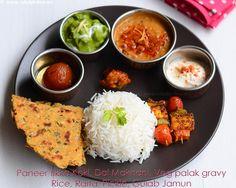 Indian lunch menu idea with paneer tikka, koki (Sindhi style flatbread with wheat flour, onion, green chilli) dal makhani, vegetable palak gravy, gulab jamun, rice, raita, pickle.