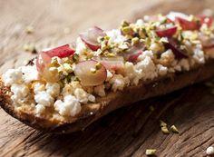2 fatias de pão italiano (ou ciabatta), fatiado com 1cm de altura    200g de queijo de cabra (crotin)    1/2 xícara (chá) de pistache, picado    1 cacho de uvas roxas sem caroço, cortadas ao meio    2 colheres (sopa) de mel    OPCIONAL: 4 figos cortados em rodelas    Azeite e pimenta do reino a gosto