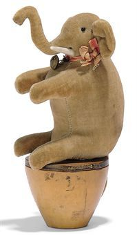 A STEIFF EARLY VELVET ELEPHANT SKITTLE, grey, black bead eyes, bone tusks, ribbon with bell, on turned tapering wooden base and elephant button, circa 1904-5.