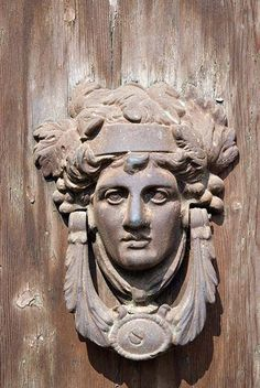 France, Alsace, Old copper door knocker with human face on wooden door