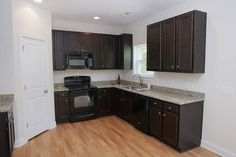 kitchens with black appliances photos | Dark cabinets and black on black appliances highlight the kitchen of ...