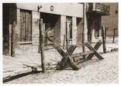 """""""View of the entrance to the Gypsy camp on Brzezinska Street in the Lodz ghetto after its liquidation. In the fall of 1941, 5007 Austrian Gypsies of the Lalleri tribe were deported to Lodz, where they were housed in a block of buildings on Brzezinska Street.  The Gypsy population remained only for a few months before being deported with the first transports to Chelmno early in 1942."""" Muzeum Sztuki w Lodzi.  US Holocaust Memorial Museum."""