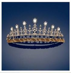 A petite diamond and natural pearl tiara, 1900. Featuring seven oval pearls in diamond clusters, on diamond foliate pinnacles, with smaller diamond spacers,  rising from two diamond bands and a brown velvet cushioning band.