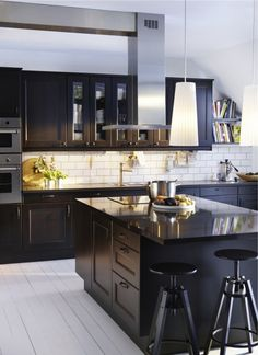 large white subway tile, dark cabinetry, awesome stools and lighting, painted wood floors